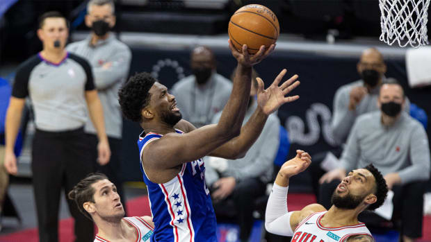 Feb 19, 2021; Philadelphia, Pennsylvania, USA; Philadelphia 76ers center Joel Embiid (21) drives for a shot against Chicago Bulls guard Denzel Valentine (45) and guard Ryan Arcidiacono (51) during the second quarter at Wells Fargo Center.