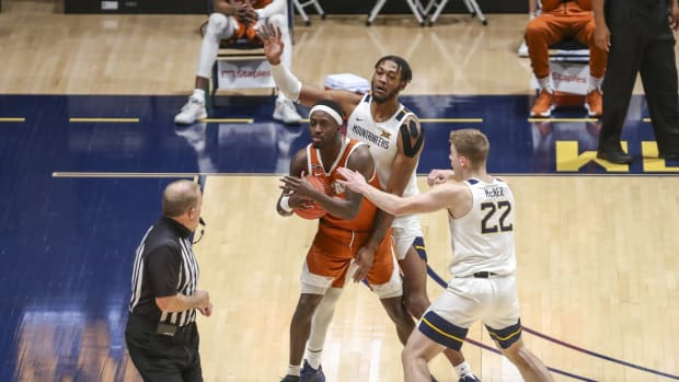 Jan 9, 2021; Morgantown, West Virginia, USA; Texas Longhorns guard Courtney Ramey (3) is pressured by West Virginia Mountaineers forward Derek Culver (1) and guard Sean McNeil (22) and calls a timeout during the second half at WVU Coliseum.