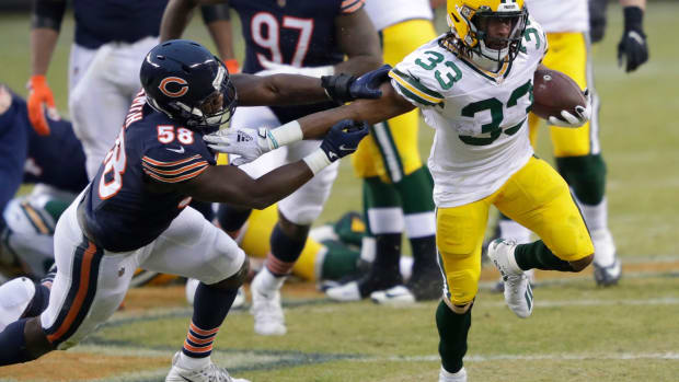 Packers running back Aaron Jones (33) runs for a gain against Chicago Bears inside linebacker Roquan Smith (58) during their football game Sunday, January 3, 2021, at Soldier Field in Chicago