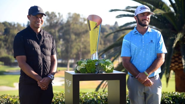 Max Homa prepares to accept winner's trophy from tournament host Tiger Woods