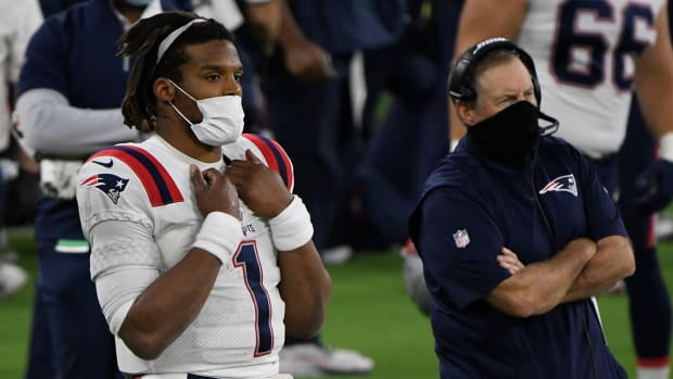 Cam Newton looks on from the sidelines with head coach Bill Belichick