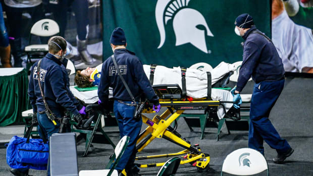 Referee Angie Enlund is taken away on a stretcher after Enlund was knocked over on the court by a Rutgers player at the end of the Michigan State vs. Rutgers women's basketball game on Wednesday, Feb. 24, 2021, at the Breslin Center in East Lansing.