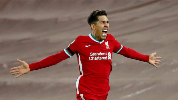 LIVERPOOL, ENGLAND - DECEMBER 16:Roberto Firmino of Liverpool celebrates after scoring their team's second goal during the Premier League match between Liverpool and Tottenham Hotspur at Anfield on December 16, 2020 in Liverpool, England. A limited number of fans (2000) are welcomed back to stadiums to watch elite football across England. This was following easing of restrictions on spectators in tiers one and two areas only. (Photo by Clive Brunskill/Getty Images)