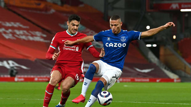 LIVERPOOL, ENGLAND - FEBRUARY 20: Richarlison of Everton is challenged by Ozan Kabak of Liverpool during the Premier League match between Liverpool and Everton at Anfield on February 20, 2021 in Liverpool, England. Sporting stadiums around the UK remain under strict restrictions due to the Coronavirus Pandemic as Government social distancing laws prohibit fans inside venues resulting in games being played behind closed doors. (Photo by Paul Ellis - Pool/Getty Images)