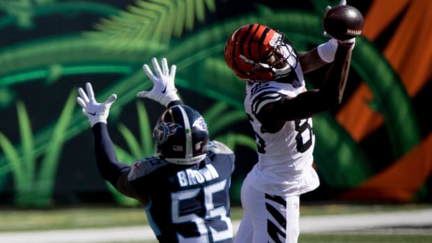 The ball goes through the hands of Cincinnati Bengals wide receiver Tee Higgins (85) as Tennessee Titans inside linebacker Jayon Brown (55) attempts to intercept it in the first quarter of the NFL game between Cincinnati Bengals and Tennessee Titans on Sunday, Nov. 1, 2020, in Cincinnati.