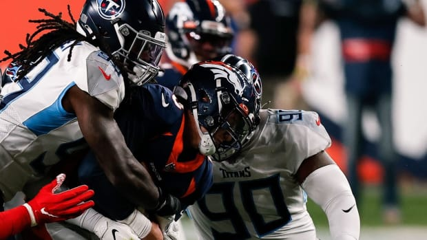 Denver Broncos quarterback Drew Lock (3) is tackled by Tennessee Titans linebacker Jadeveon Clowney (99) and defensive tackle Jeffery Simmons (98) and defensive end DaQuan Jones (90) in the first quarter at Empower Field at Mile High.
