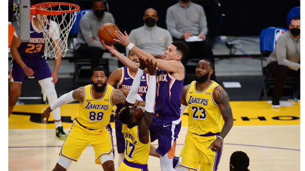 Mar 2, 2021; Los Angeles, California, USA; Phoenix Suns guard Devin Booker (1) moves in for a basket against Los Angeles Lakers guard Dennis Schroder (17) forward Markieff Morris (88) and forward LeBron James (23) during the first half at Staples Center.