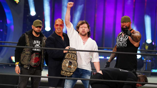 AEW's Kenny Omega poses in the ring with Don Callis and the Good Brothers