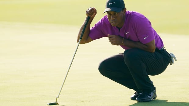 Nov 14, 2020; Augusta, Georgia, USA; Tiger Woods lines up his putt on the 17th green during the third round of The Masters golf tournament at Augusta National GC.