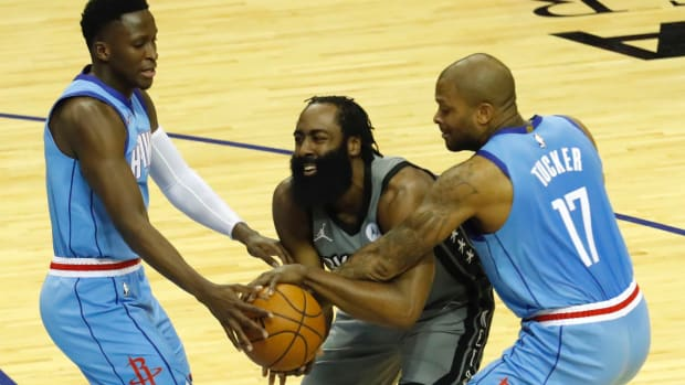 James Harden #13 of the Brooklyn Nets is pressured by P.J. Tucker #17 of the Houston Rockets and Victor Oladipo #7 at Toyota Center on March 03, 2021 in Houston, Texas.