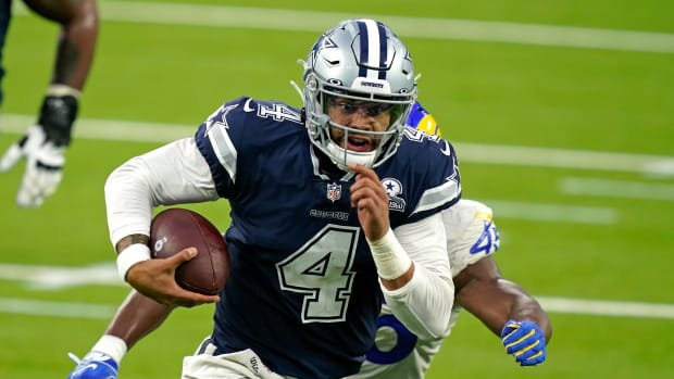 Dak Prescott runs from a Rams defender during a game
