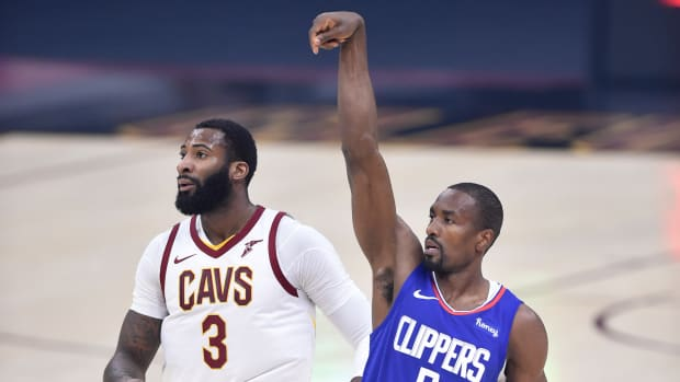 Feb 3, 2021; Cleveland, Ohio, USA; LA Clippers center Serge Ibaka (9) reacts to his three-point basket beside Cleveland Cavaliers center Andre Drummond (3) in the first quarter at Rocket Mortgage FieldHouse. Mandatory Credit: David Richard-USA TODAY Sports