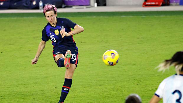 Megan Rapinoe kicks a soccer ball.