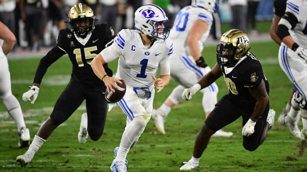 Dec 22, 2020; Boca Raton, Florida, USA; Brigham Young Cougars quarterback Zach Wilson (1) scrambles with the ball against the UCF Knights during the first half at FAU Stadium.