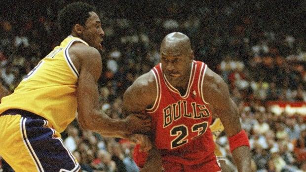 Michael Jordan is held up by Los Angeles Lakers Kobe Bryant in 1998.