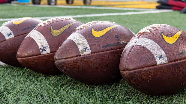 Four footballs laying on a turf field