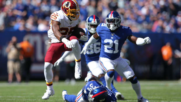 Sep 29, 2019; East Rutherford, NJ, USA; Washington Redskins running back Chris Thompson (25) runs the ball against New York Giants cornerback Grant Haley (34) and safety Jabrill Peppers (21) during the second quarter at MetLife Stadium.
