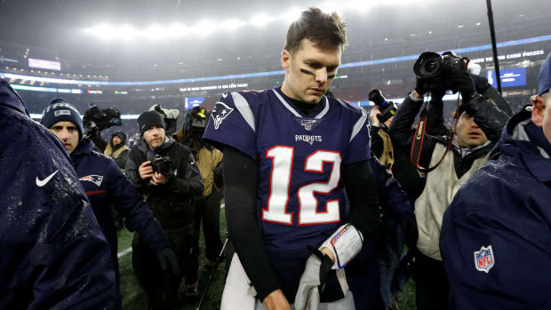 Patriots QB Tom Brady walks off the field after playoff loss to the Titans