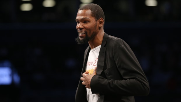 Nets star Kevin Durant on the sideline in a blazer and t-shirt