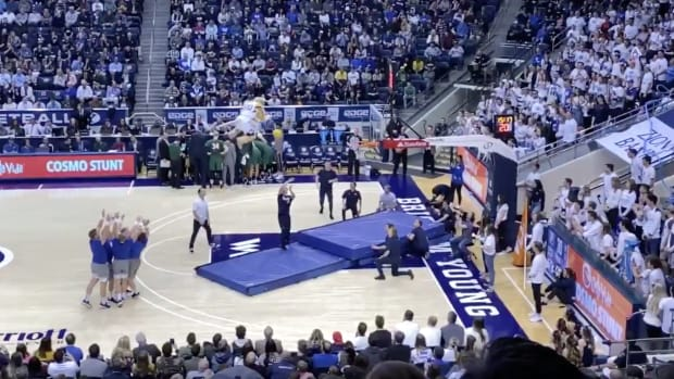 Screencap from video of BYU cheerleader throwing mascot into the air for a dunk