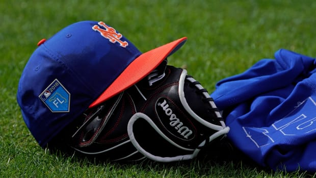 A New York Mets player's hat and glove on the grass during spring training