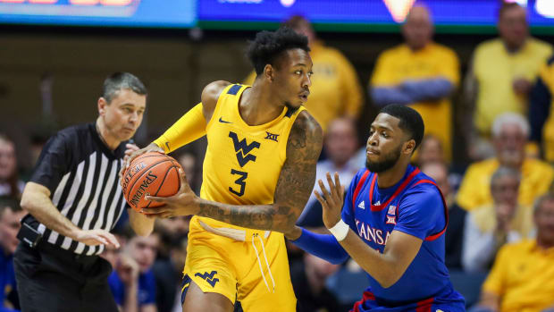 West Virginia Mountaineers forward Gabe Osabuohien (3) looks to pass while defended by Kansas Jayhawks guard Isaiah Moss (4) during the first half at WVU Coliseum.