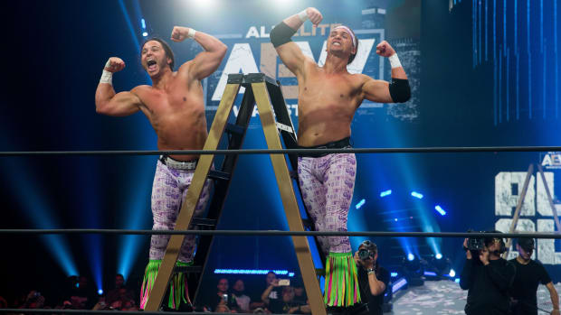 Matt and Nick Jackson (Massie) of AEW's The Young Bucks stand on a ladder in the ring celebrating