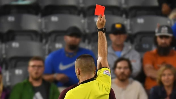 A soccer referee issues a red card, with his back to the camera