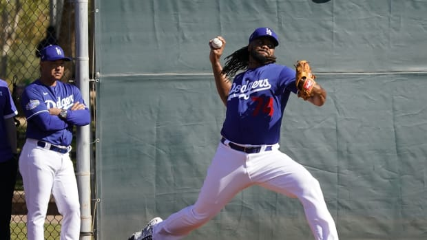 Feb 14, 2020; Glendale, Arizona, USA; Los Angeles Dodgers relief pitcher Kenley Jansen (74) throws in the bullpen as manager Dave Roberts (left) looks on during spring training. Mandatory Credit: Rick Scuteri-USA TODAY Sports