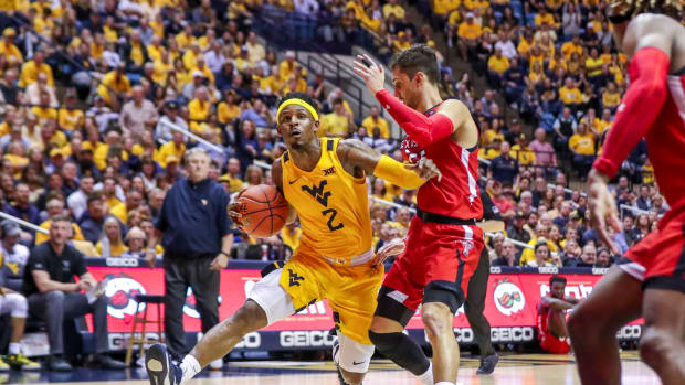 West Virginia Mountaineers guard Brandon Knapper (2) drives down the lane and is defended by Texas Tech Red Raiders guard Davide Moretti (25) during the second half at WVU Coliseum.