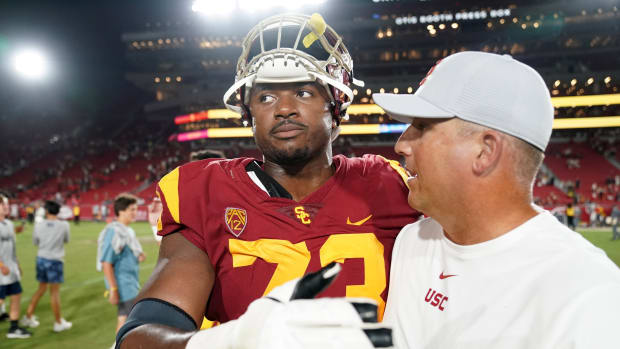Aug 31, 2019; Los Angeles, CA, USA; Southern California Trojans head coach Clay Helton (right) and offensive tackle Austin Jackson (73) embrace after the game against the Fresno State Bulldogs at Los Angeles Memorial Coliseum. USC defeated Fresno State 31-23.