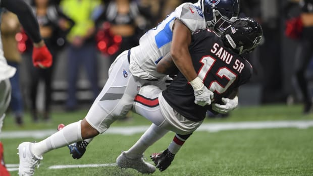 Tennessee Titans linebacker Reggie Gilbert (93) tackles Atlanta Falcons wide receiver Mohamed Sanu (12) during the second half at Mercedes-Benz Stadium.