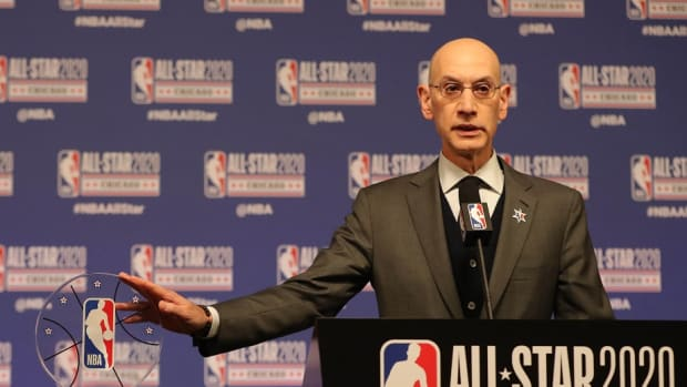 NBA commissioner Adam Silver stands with the Kobe Bryant All-Star Game MVP trophy.