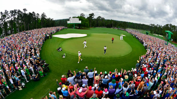 Tiger Woods walks off the 18th green after winning The Masters golf tournament at Augusta National Golf Club
