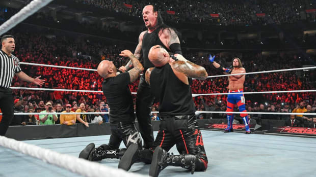 WWE's The Undertaker chokes Luke Gallows and Karl Anderson in the ring on Raw as AJ Styles looks on