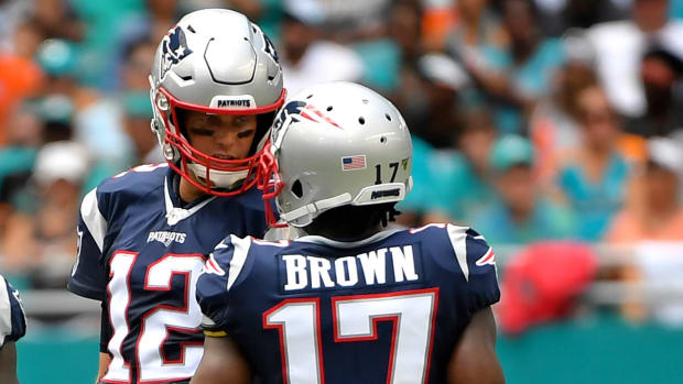 New England Patriots quarterback Tom Brady talks with New wide receiver Antonio Brown near the line of scrimmage against the Miami Dolphins during the first half at Hard Rock Stadium.