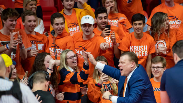 Illinois Fighting Illini head coach Brad Underwood celebrates with fans after a game against the Iowa Hawkeyes at State Farm Center.