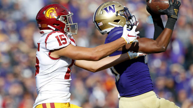 Washington safety Cam Williams intercepts a pass intended for USC's London Drake.