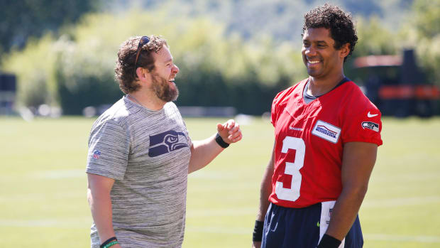 Seahawks GM John Schneider jokes with Russell Wilson during practice