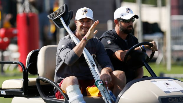 Redskins QB Alex Smith rides in a golf cart with crutches as he recovers from a life-threatening leg injury
