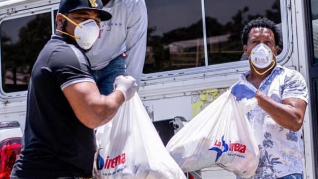 Edwin Encarnacion and Pedro Martinez distribute supplies to communities in the Dominican Republic.