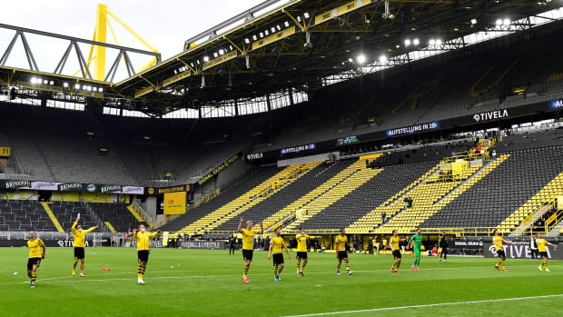 Dortmund players salute the empty Yellow Wall at Signal Iduna Park