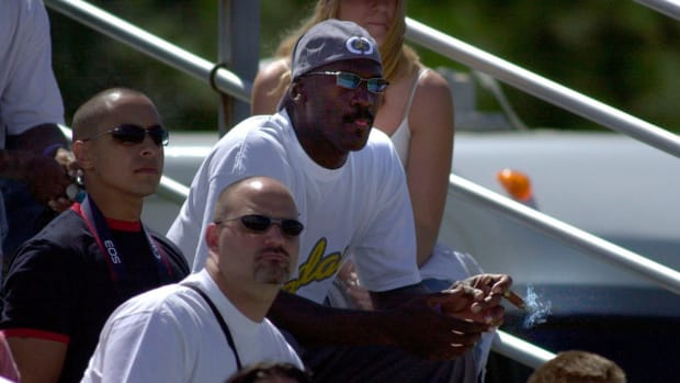 Michael Jordan smokes a cigar at an auto racing event in 2004