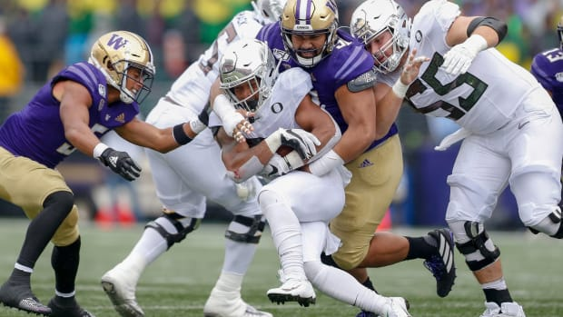Tuli Letuligasenoa swallows up an Oregon runner. The Washington defensive tackle is looking for a breakout year.