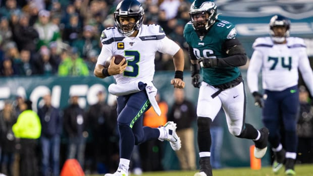 Russell Wilson scrambles away from an Eagles defender.