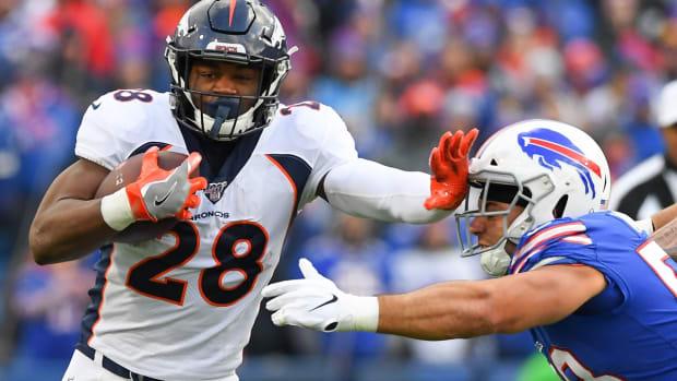 Denver Broncos running back Royce Freeman (28) runs with the ball as Buffalo Bills outside linebacker Matt Milano (58) defends during the third quarter at New Era Field.
