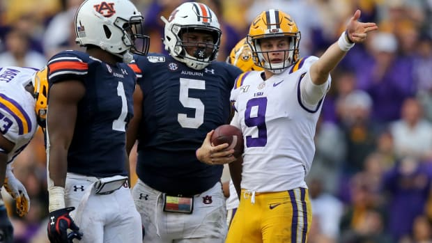 Oct 26, 2019; Baton Rouge, LA, USA; LSU Tigers quarterback Joe Burrow (9) signals a first down in front of Auburn Tigers defensive end Big Kat Bryant (1) and defensive tackle Derrick Brown (5) in the second half at Tiger Stadium. Mandatory Credit: Chuck Cook-USA TODAY Sports