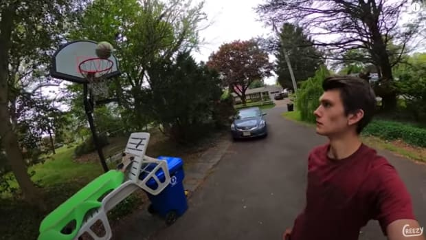 A basketball going through a hoop with a man standing by