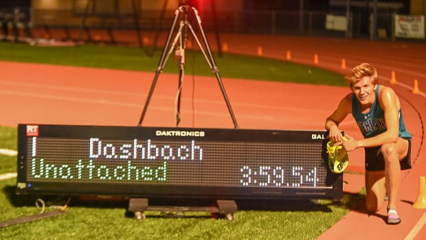 Leo Daschbach poses with the finish line clock after becoming the 11th U.S. high school runner to break four minutes for the mile.