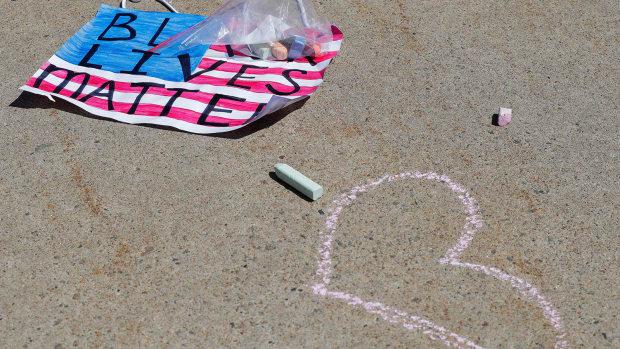 A sidewalk chalk heart next to a sign reading Black Lives Matter